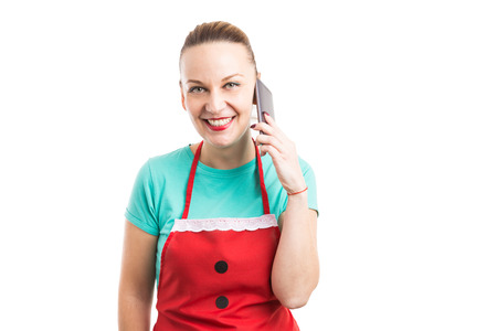 Happy friendly face contact female person wearing red apron holding phone and smiling trustworthy isolated on white Stock Photo