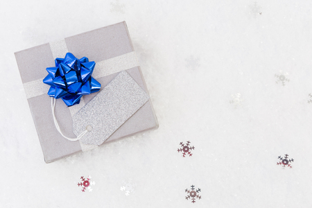 happy new year or christmas gift on snow and copyspace with empty blank label or tag