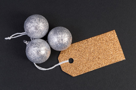 Holiday blank golden tag or label with silver balls as greeting copyspace and text area concept