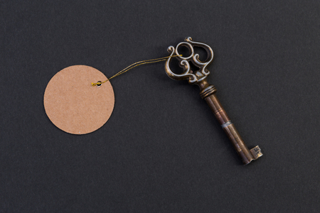 Old vintage key with blank empty tag or label on black background as hotel and real estate concept Stock Photo