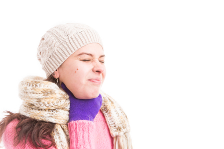Woman suffering of throat and swallowing pain wearing warm clothes as contagious flu virus concept