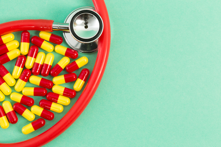 Red and yellow antibiotics and stethoscope on green medical paper background