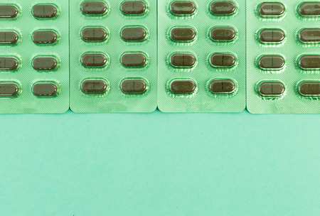 Green capsules on blisters and bottom copyspace as natural homeopathic healtcare concept
