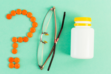 Question mark made of tablets and spectacles near bottle of pills as doctor prescription daily dose concept Stock Photo