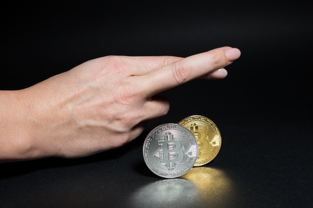 Bitcoins and fingers crossed as hope gesture for more growth of the virtual currency decentralized money Stockfoto