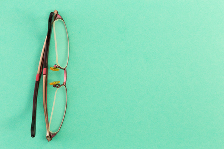 Reading goggles or spectacles on green table board as medical optics concept Stock Photo