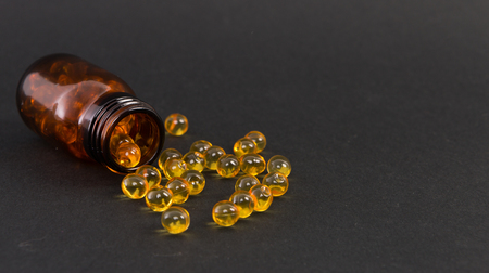 Spilled yellow transparent golden capsules of vitamine on dark background as skin treatment concept