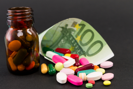 Hundred euros wrapped with pills and capsules as expensive medical treatment concept