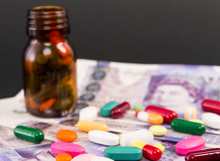 Spilled pills on british pounds banknotes as great britain medical insurance or expensive pharmacy concept Banque d'images