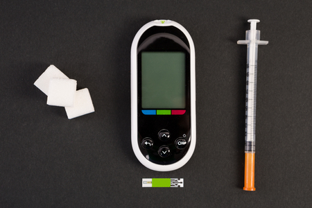 Insulin syringe glucometer and white sugar cubes on black background as diabet and hypoglycemia concept