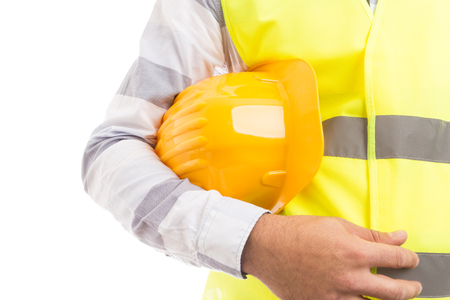 Closeup of a constructor holding yellow worker hat underarm on white copyspace and text area