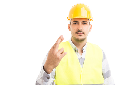 Builder or constructor making bad luck gesture with fingers crossed on one hand isolated on white background Stock Photo
