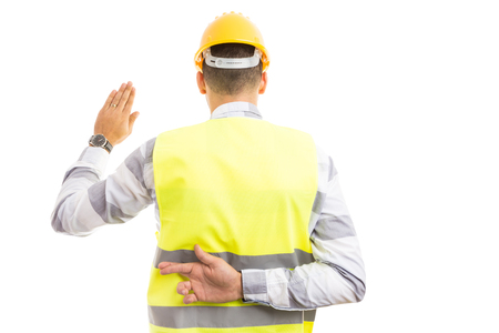 Cunning builder making fake oath or vow hesture with fingers crossed behind back isolated on white background