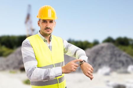 Baustellemanager, der Uhr als spätes Konzept auf Hintergrund im Freien zeigt