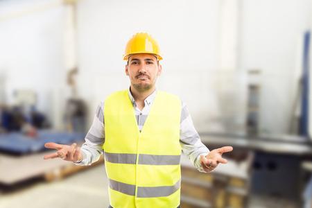 Perplejo trabajador pidiendo gesto como técnico no capacitado electricista persona concepto sobre fondo de empresa o fábrica Foto de archivo