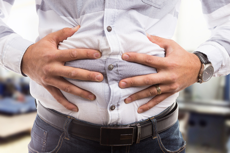 Man pressing grabbing bloated abdomen or belly as cramp flatulence constipation problem