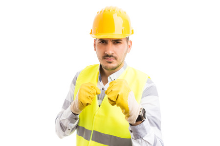 Menacing worker showing fists in aggressive mode as a fighter or boxer isolated on white background