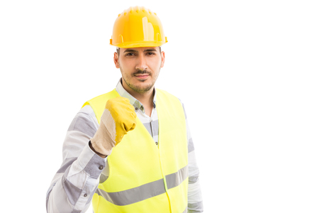 Threatening and menacing builder or worker showing fist in aggressive way isolated on white background