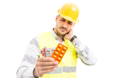 Hurt engineer or constructor holding pills blisters as sick ill builder concept isolated on white background Stock Photo