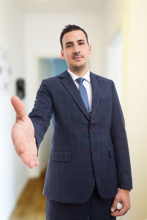 Real estate manager making handshake gesture as deal concept smiling trustworthy on home indoors background