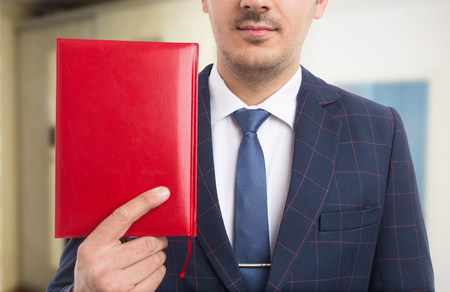 Anonymous pastor holding red bible or notebook as believer concept on indoors background