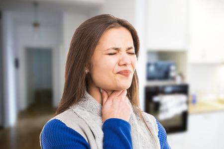 Junge Frau, die starken Halsschmerz wegen Grippekälte als Schluckbeschwerden-Ausdruckskonzept auf Innenraumhintergrund erfährt