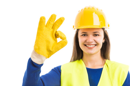 Young female constructor or contractor showing ok sign gesture and smiling as successful building concept isolated on white background Фото со стока