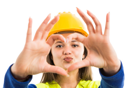 Young pretty woman architect or engineer showing heart sign and kiss lips gesture as cheerful constructor concept isolated on white background