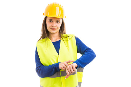 Young female engineer or architect making late time gesture as unhappy bossy manager concept isolated on white background Фото со стока