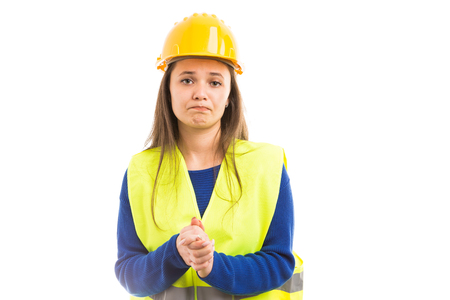 Young female engineer or architect begging by making please gesture as asking for favor concept isolated on white background