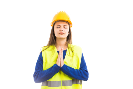 Young attractive woman architect or engineer praying with hands together as religious professional female concept isolated on white background