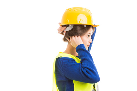 Young female architect or engineer tucking hair under helmet as preparing and getting ready for work concept isolated on white background Stock Photo