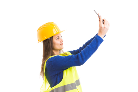 Young attractive female architect or engineer taking a selfie or a video call using smartphone as  technology concept isolated on white background