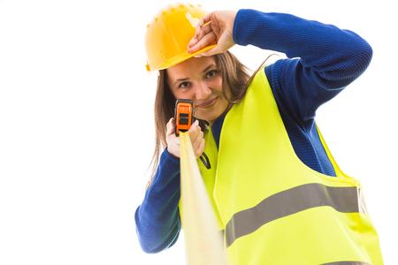 Junger attraktiver weiblicher Architekt oder Ingenieur, der Maßband hält und Helm als glückliches Erbauerkonzept lokalisiert auf weißem Hintergrund hält