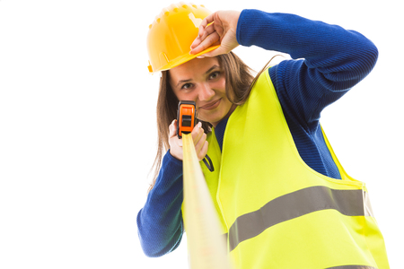 Young attractive female architect or engineer holding measuring tape and touching helmet as happy builder concept isolated on white background