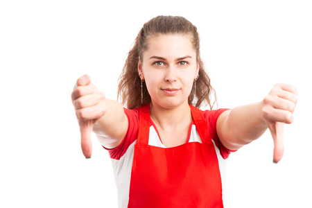 Young female supermarket worker showing thumbs down as denial rejection gesture concept isolated on white background
