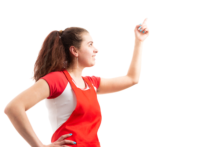 Young female supermarket employee pointing up at empty area as presenting or indicating concept isolated on white background