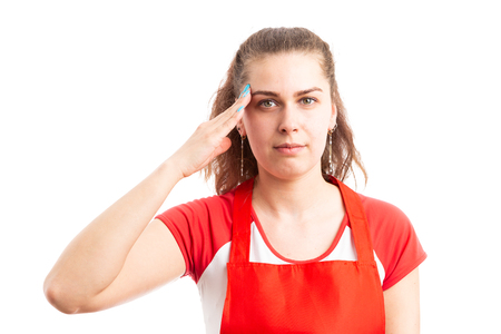 Young female supermarket or hypermarket employee military saluting as serious retail worker concept isolated on white background Stock Photo