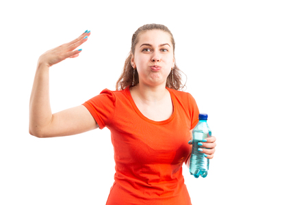 Young woman suffering health problem from high temperature heat holding bottle of water and making hot gesture as overheat concept isolated on white background