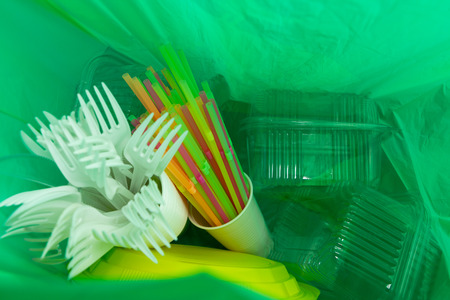 Inside of green plastic bag with single use cutlery plates straws cup and package boxes as ecology environment waste pollution concept