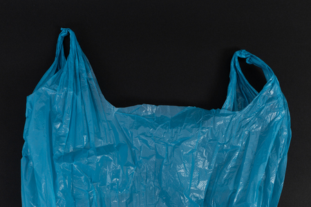 Used crumpled single use blue plastic bag with handles as waste pollution environment ecology concept isolated on black background Archivio Fotografico
