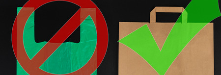 Biodegradable versus single use waste choice concept with green plastic and brown paper bags isolated on black background Archivio Fotografico