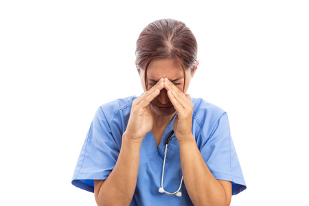 Woman nurse holding head sinuses with hands suffering from cold or flu as sick female doctor concept isolated on white background Stock Photo