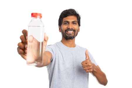 Friendly indian man showing thumb up gesture with water bottle in one hand isolated on white background as stay hydrated concept Stock fotó