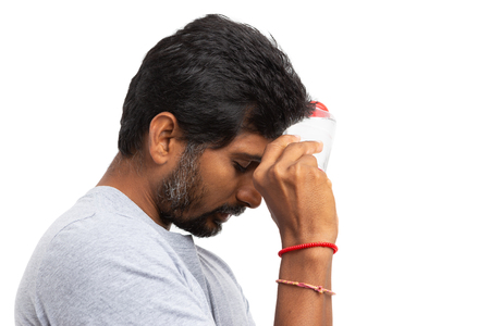 Indian male touching forehead with plastic cold water bottle to refresh in the hot summer isolated on white as stay hydrated concept
