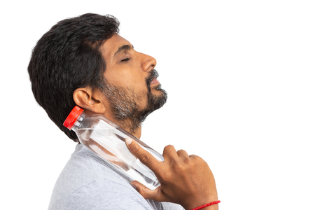 Indian person cooling down neck by touching it with a cold water bottle isolated on white background as summer refreshment concept Archivio Fotografico