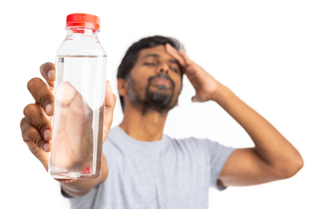 Focused water bottle held by indian man touching forehead in pain as heat-stroke or sun-stroke concept isolated on white studio background Stok Fotoğraf