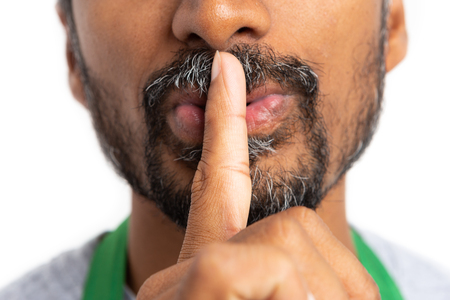 Close-up silence gesture with index finger on mouth made by hypermarket or supermarket employee isolated on white background Foto de archivo