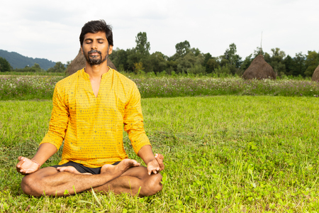 Indian relaxed yogu with closed eyes to focus sitting cross-legged in lotus pose with natural background Stock Photo