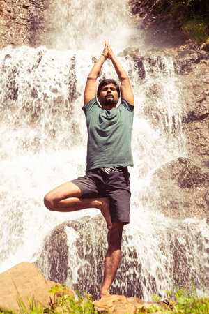 Indian yogi with closed eyes standing in tree position near waterfalls as relaxed lifestyle concept with natural background
